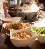 Stir fry ingredients alongside a wok at the Islands Dining Room at Loews Royal Pacific Resort.