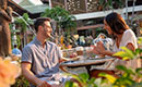 A couple dines together in the outdoor courtyard at Loews Royal Pacific Resort in Orlando.